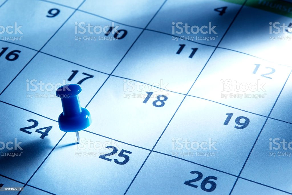 Blue tinted image of thumbtack in calendar with light rays stock photo