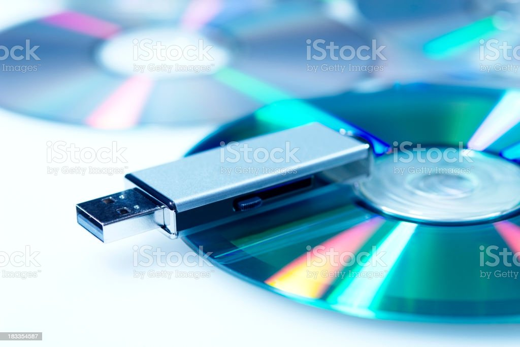Blue tinted image of USB flash memory with CD stock photo