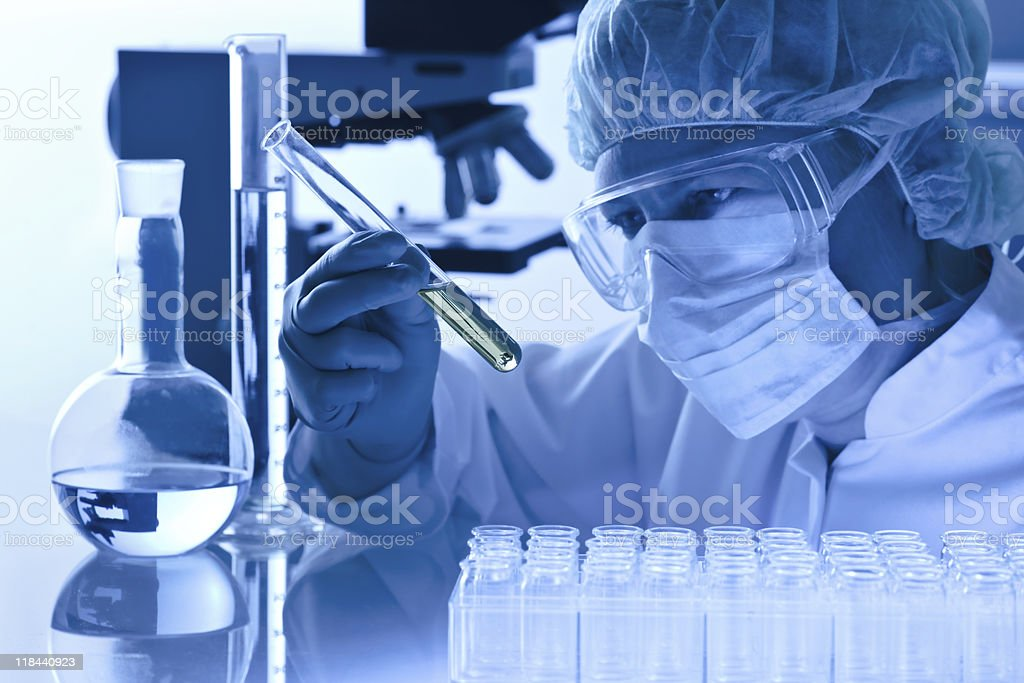 Blue tinted photo of a worker in a mask in a laboratory royalty-free stock photo