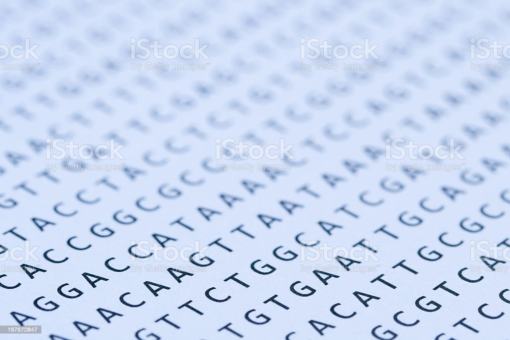 Blue tinted printout of DNA nucleotide sequence on paper stock photo