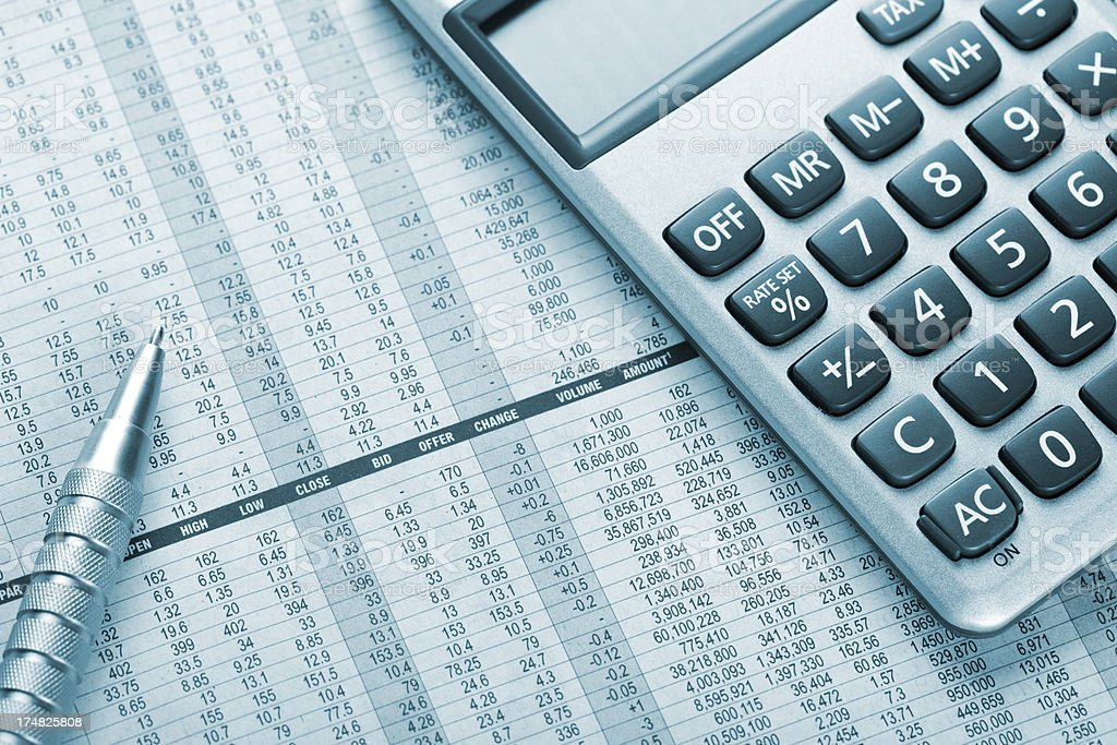 Blue tinted stock market analysis with pen and calculator stock photo