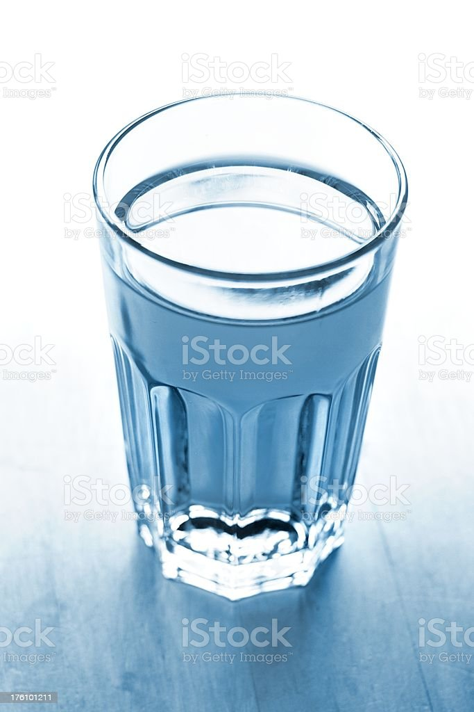 blue toned full waterglas with white background royalty-free stock photo
