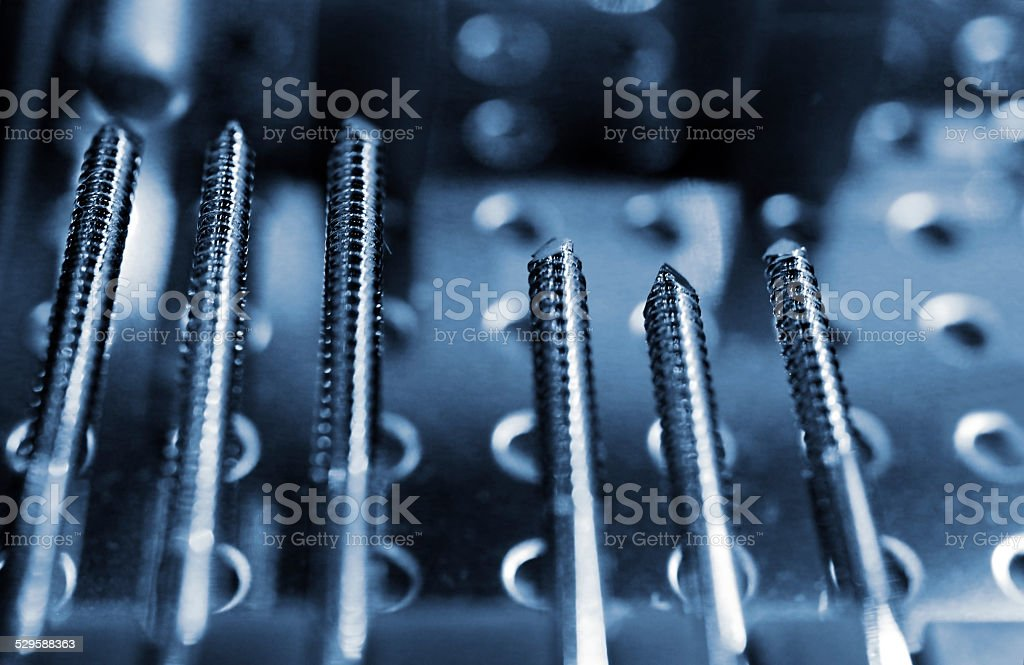 Blue toned long screws in a row stock photo