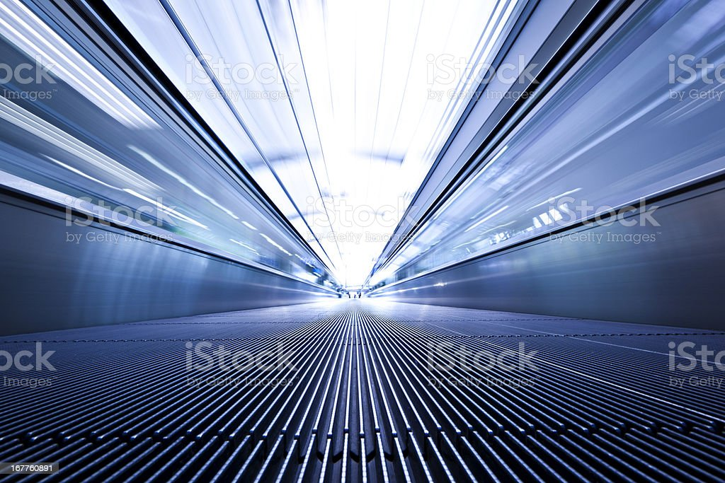 Blue toned low angle photo of moving walkway stock photo