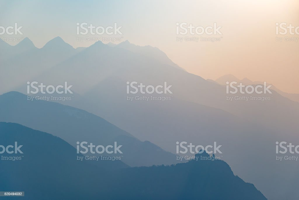 Blue toned mountain silhouette and abbey profile at sunset stock photo