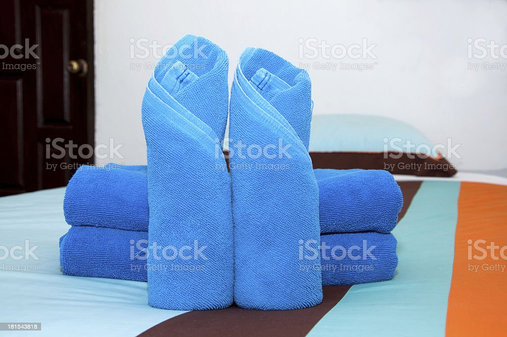 Blue towel roll is placed on the bed. royalty-free stock photo