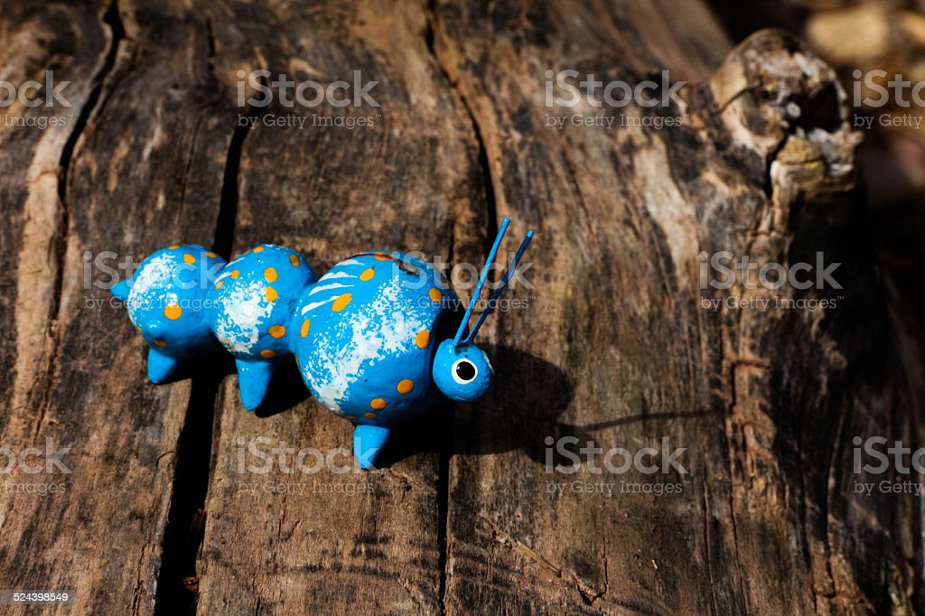 Blue toy caterpillar on a Log stock photo