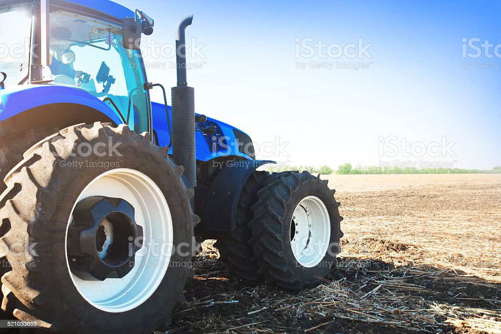 Blue tractor in a field stock photo