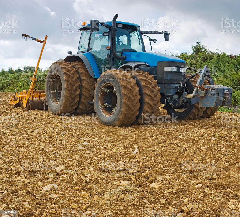 Blue tractor in plowed field royalty-free stock photo