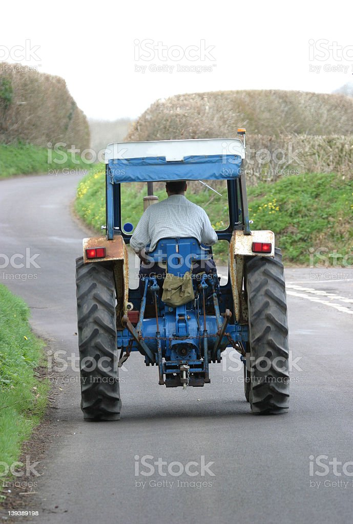 Blue tractor on road path at day time stock photo