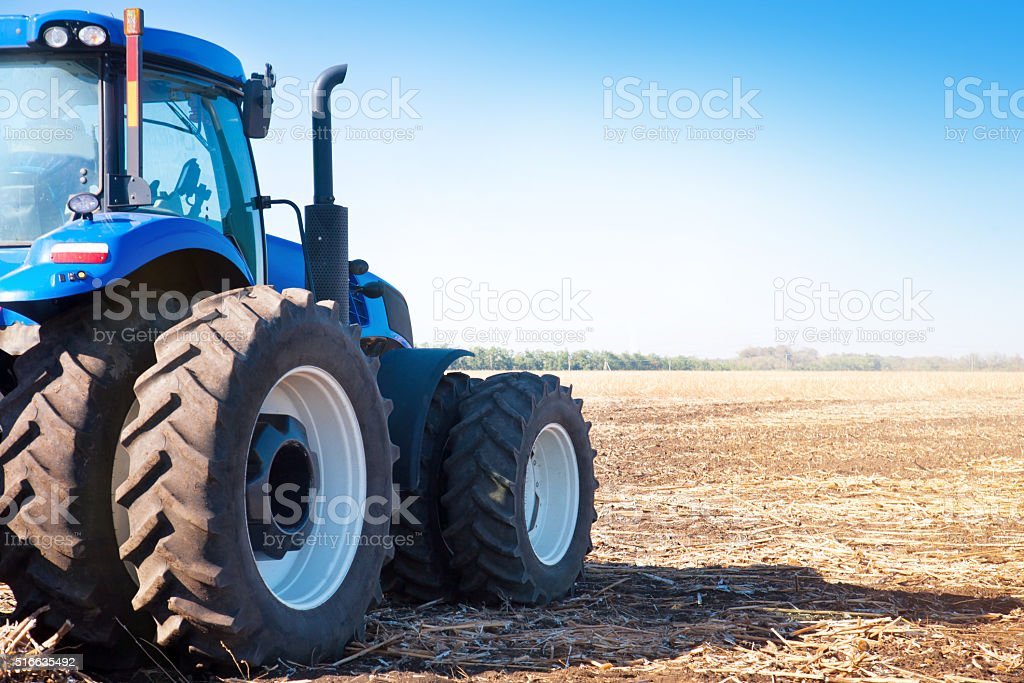 Blue tractor on the background of an empty field stock photo