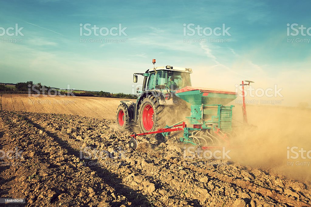 Blue tractor sowing in field stock photo