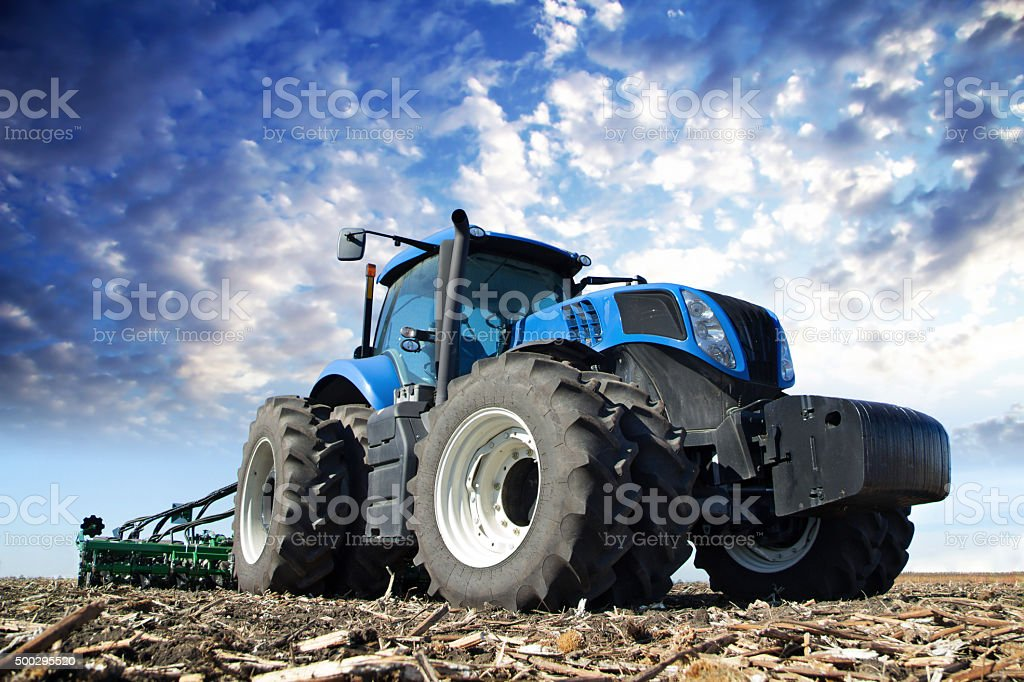 Blue tractor working on the farm stock photo