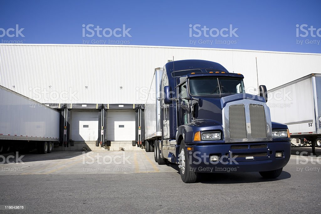 Blue Tranport Truck Docking in warehouse stock photo