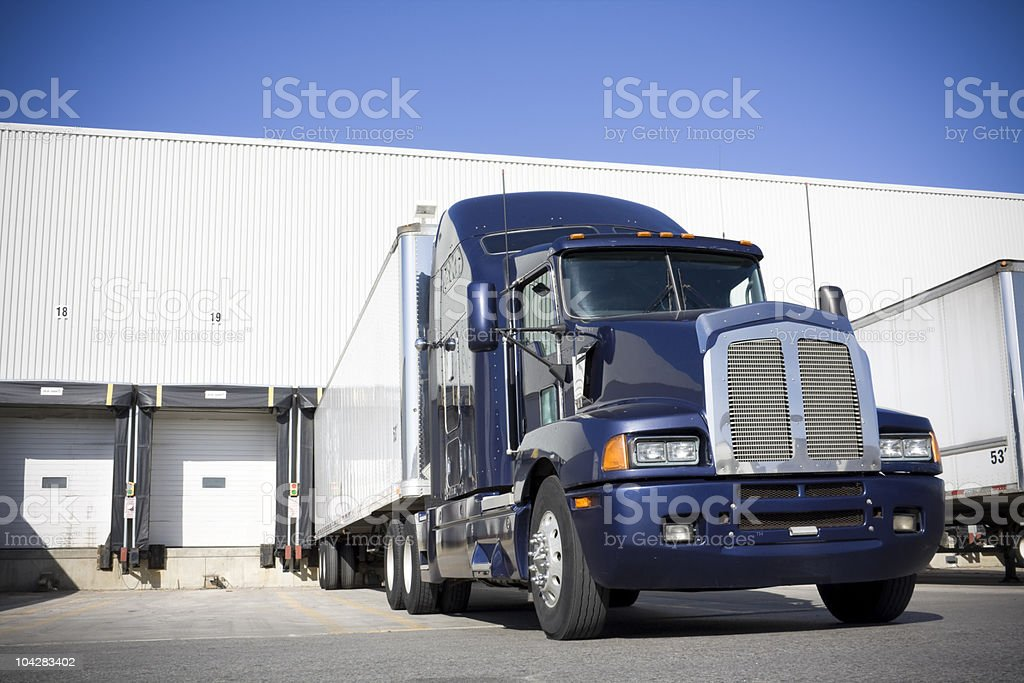 Blue Transport truck docking at warehouse stock photo