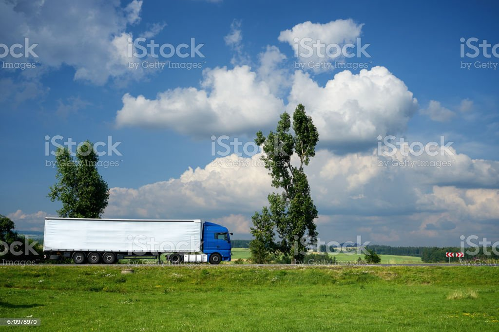 Blue truck driving on the road next to tall trees stock photo