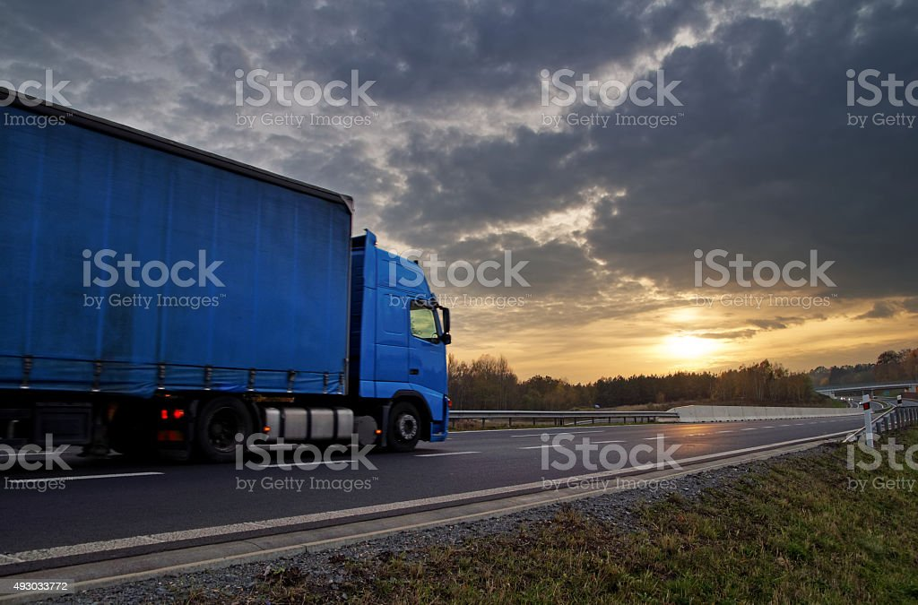 Blue truck on highway at sunset in the countryside. stock photo