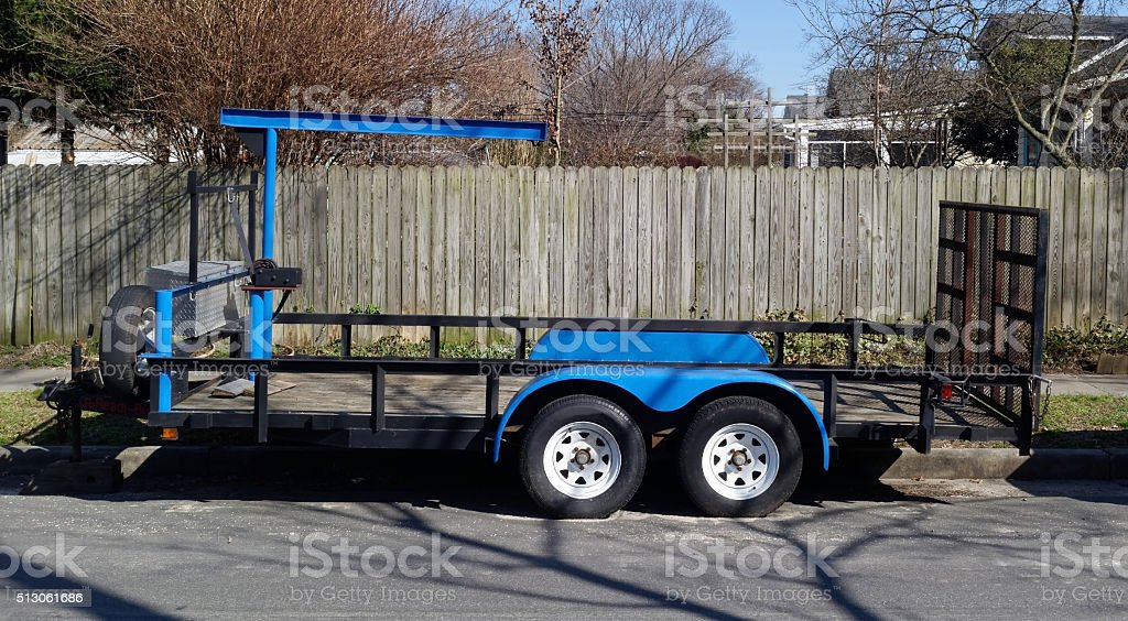 Blue Utility Trailer Parked on Residential Street stock photo