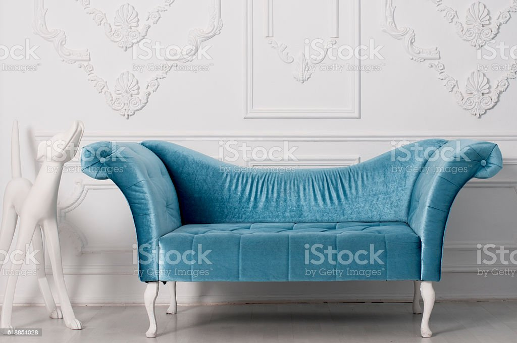 blue velvet sofa  and  and white sculpture of a dog stock photo
