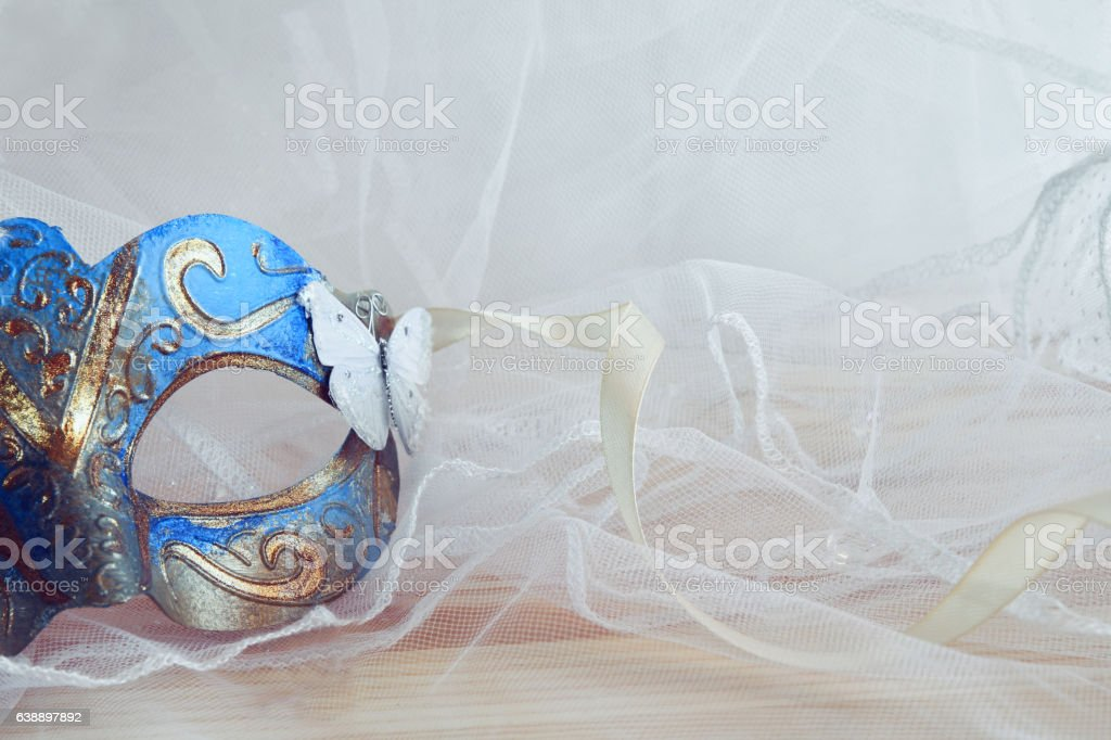 blue venetian mask next to pearls stock photo