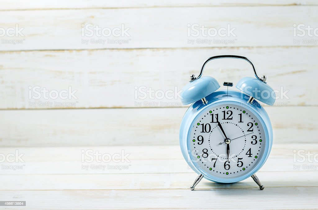 Blue Vintage Alram Clock on white wooden table stock photo