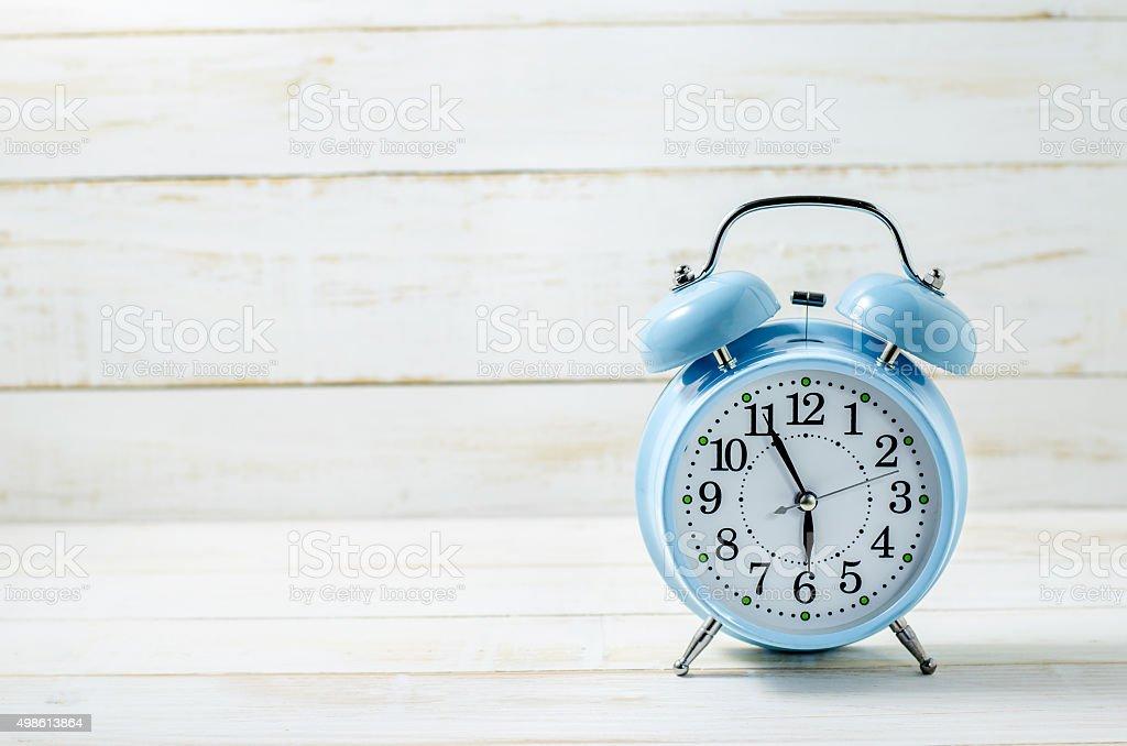 Blue Vintage Alram Clock on white wooden table stock photo
