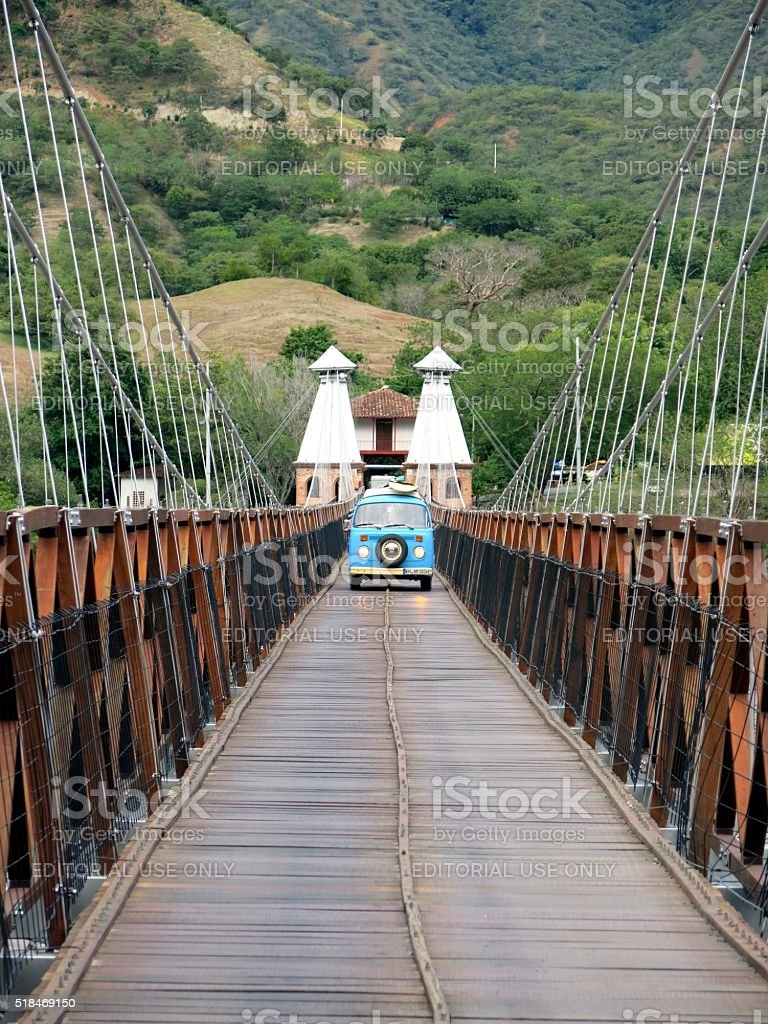 Blue VW bus driving overSuspension bridge in Colombia stock photo