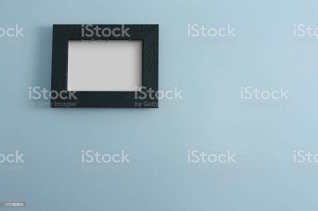 Blue Wall with Blank Black Photo Frame stock photo