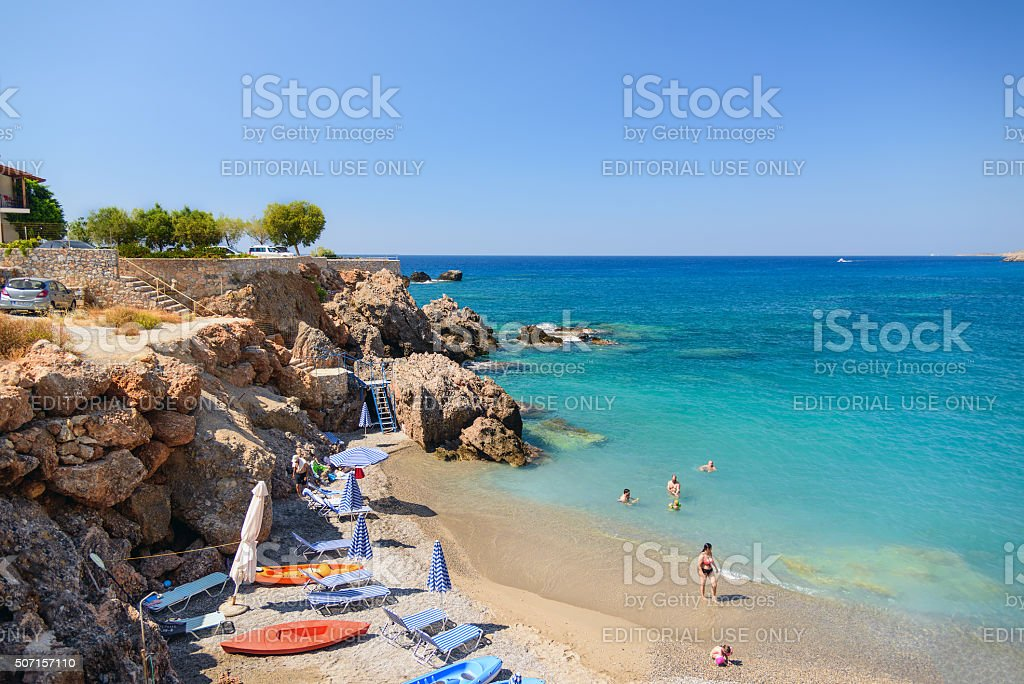Blue water bay and sandy beach with people stock photo