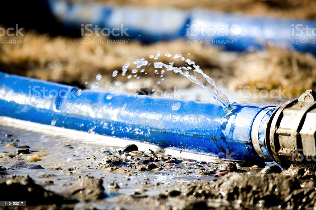 A blue water hose leaking water from a hole royalty-free stock photo