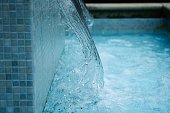 Blue water pouring into tiled pool