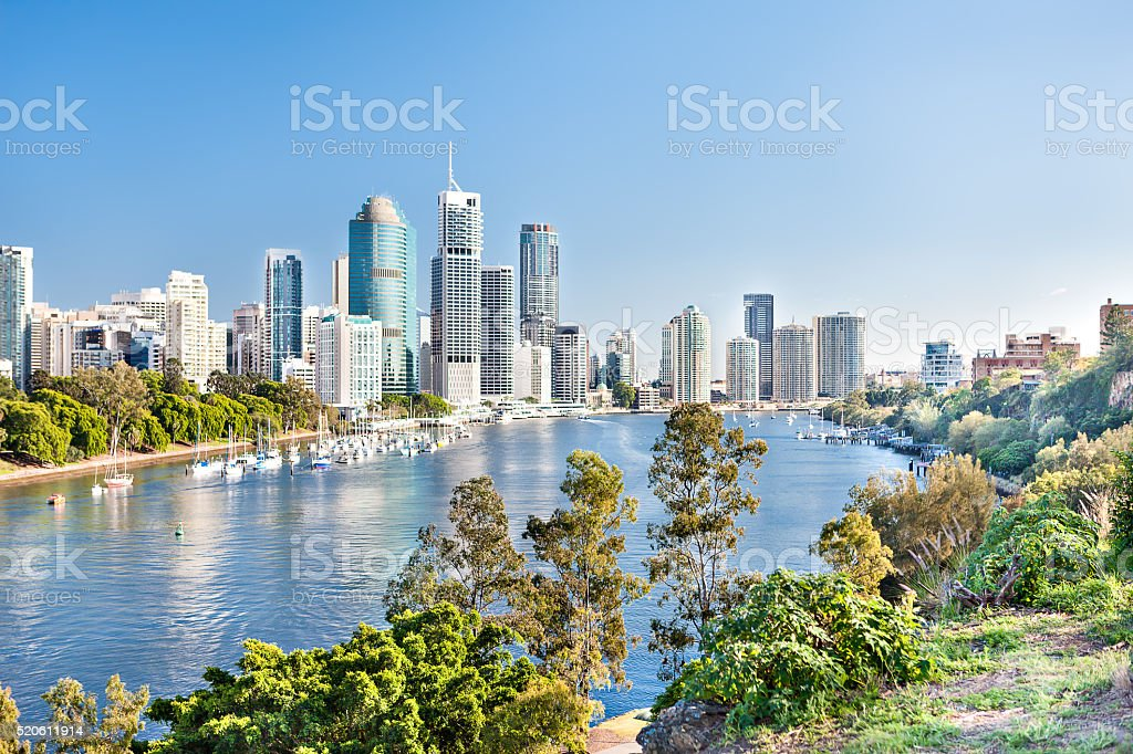 Blue water river surrounded by trees beside a modern city stock photo