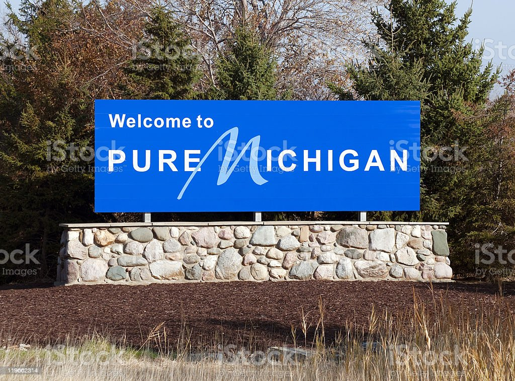 Blue welcome to pure michigan sign on a stone wall stock photo
