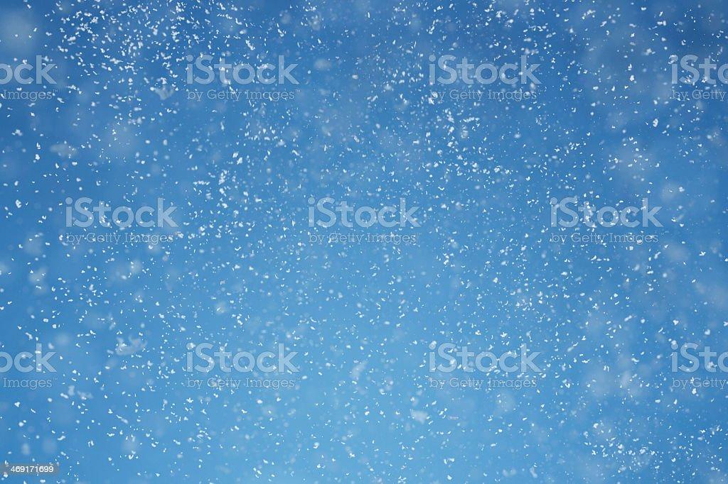 Blue winter background with tint white snow flakes stock photo