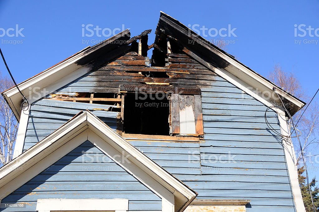 Blue wooden home with the roof burned away royalty-free stock photo
