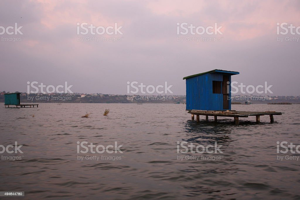 Blue wooden house stands in the water surrounded by a stock photo