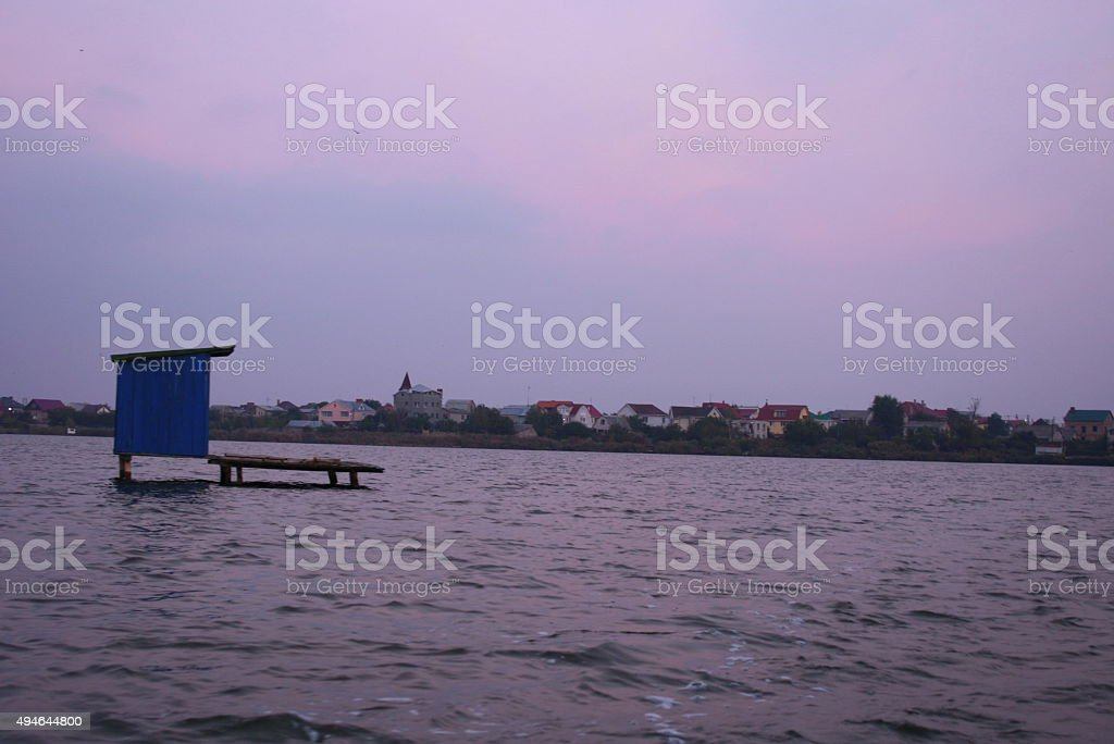 Blue wooden house stands in the water surrounded by a royalty-free stock photo