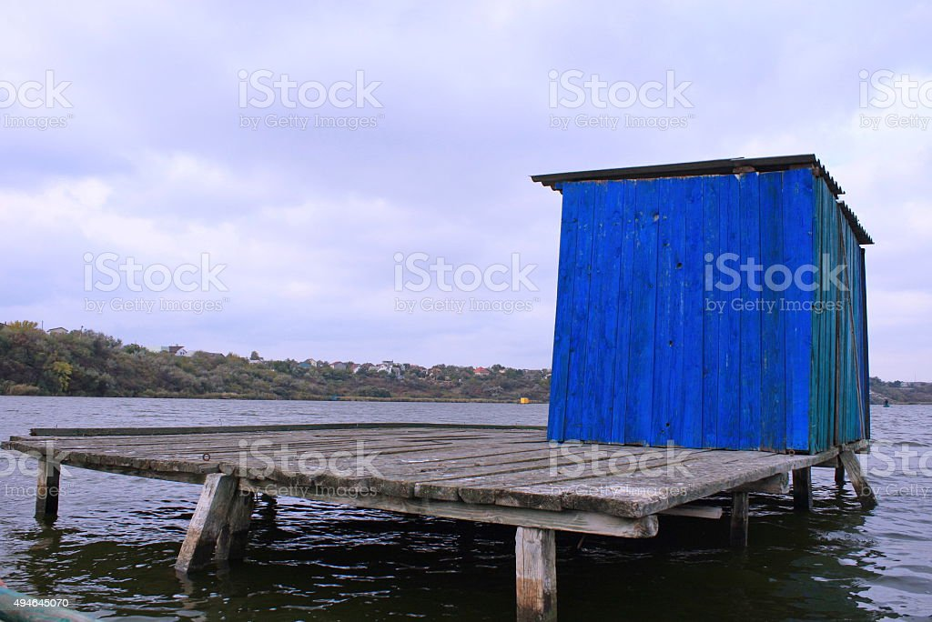 Blue wooden house stands on bridge in the middle of royalty-free stock photo