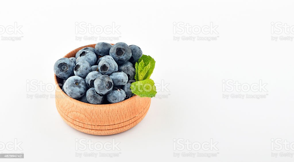 Blueberries and mint leaves in wooden bowl isolated on white royalty-free stock photo