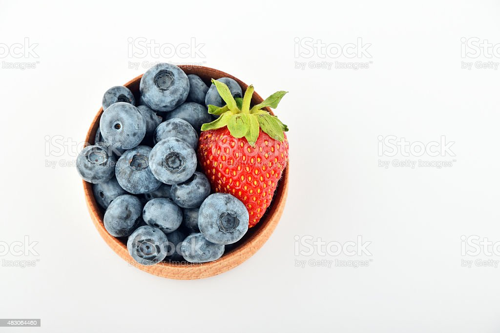 Blueberries and one strawberry in wooden bowl isolated on white royalty-free stock photo