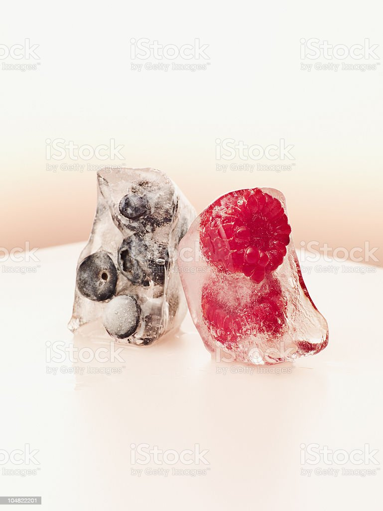 Blueberries and raspberries frozen in ice cubes royalty-free stock photo