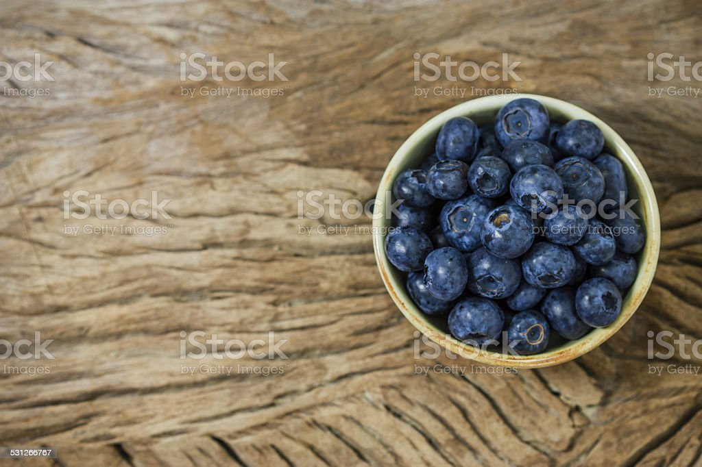 Blueberries in a bowl on a wooden table. stock photo