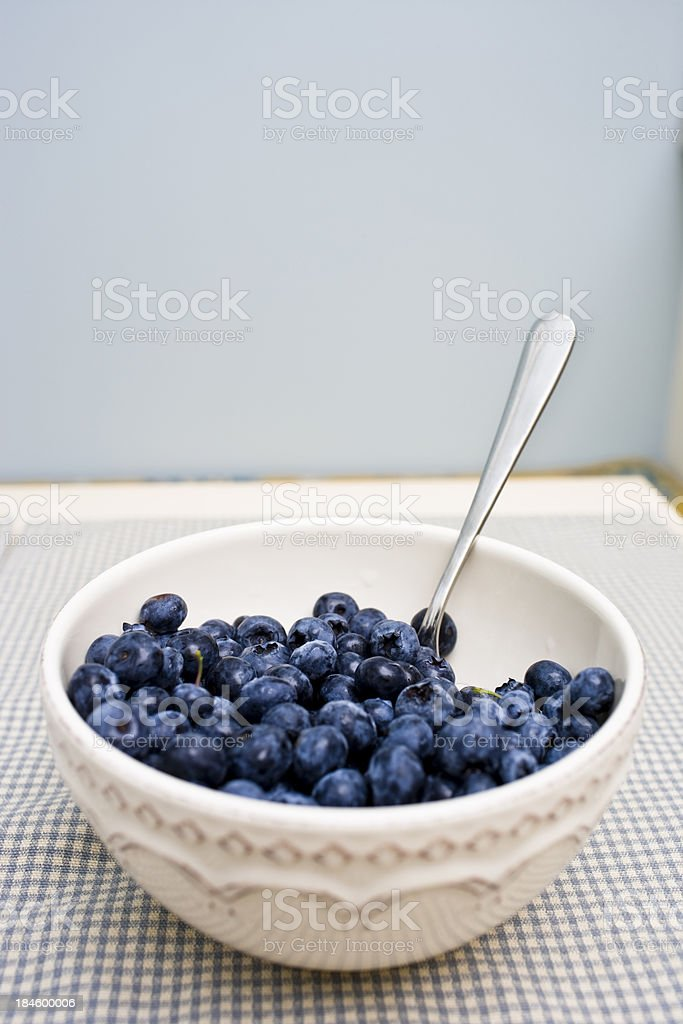 Blueberries in a bowl with a spoon royalty-free stock photo
