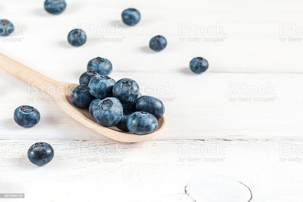 blueberries on wooden spoon close-up stock photo