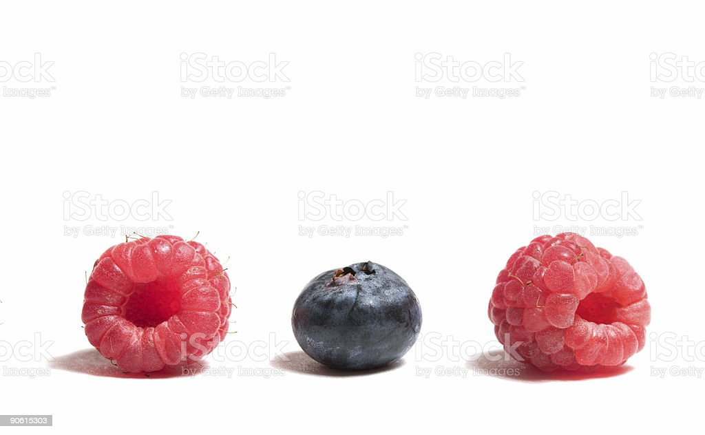 Blueberry between Two Raspberries royalty-free stock photo