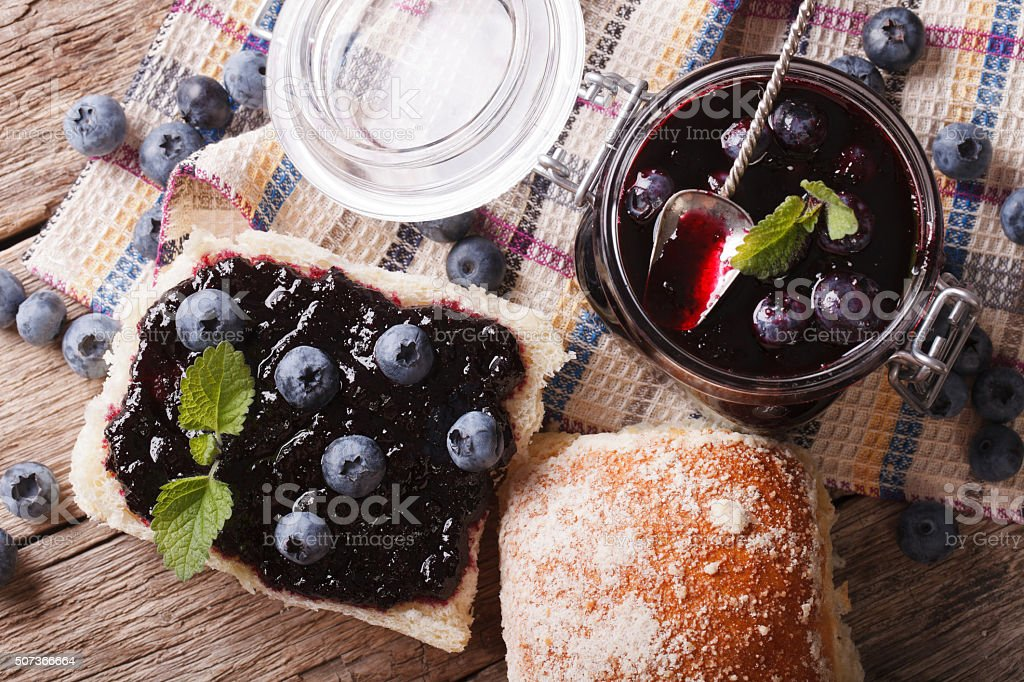 Blueberry jam and sweet bun close-up on the table stock photo