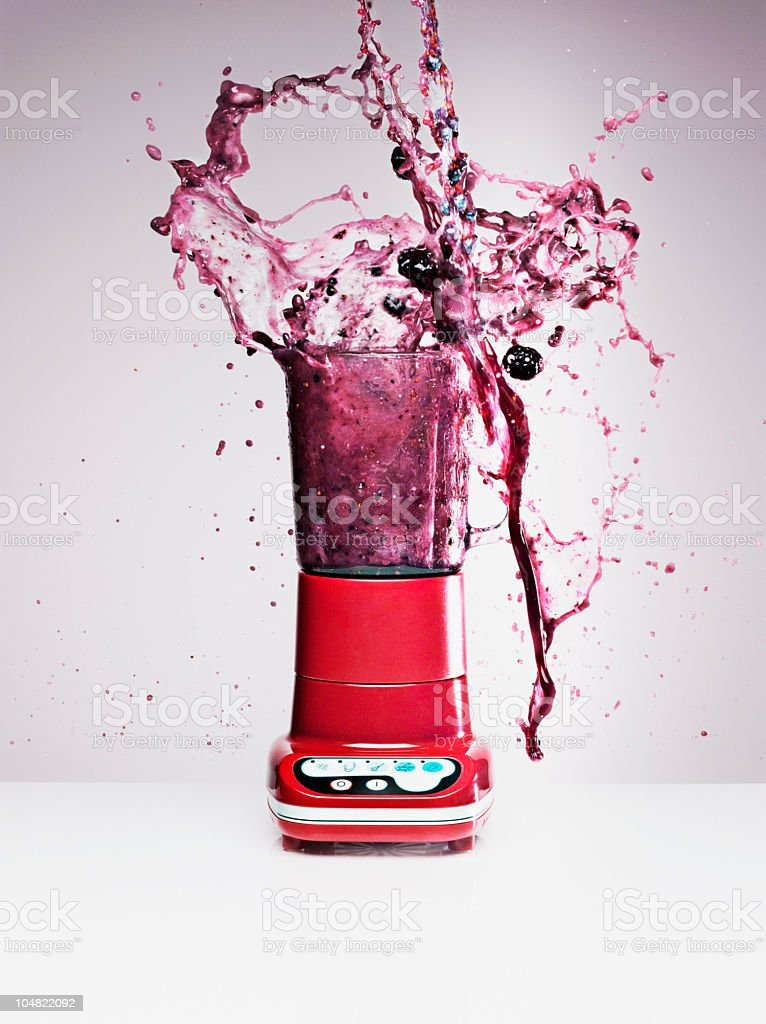 Blueberry juice splashing from blender stock photo