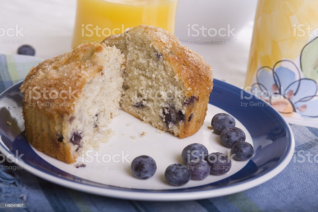 Blueberry Muffin Cut in Half with Blueberries and Orange Juice royalty-free stock photo