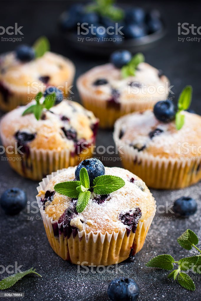 Blueberry muffins with powdered sugar and fresh berry stock photo