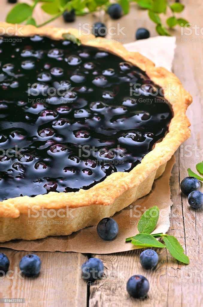 Blueberry pie and fresh berries on wooden table stock photo